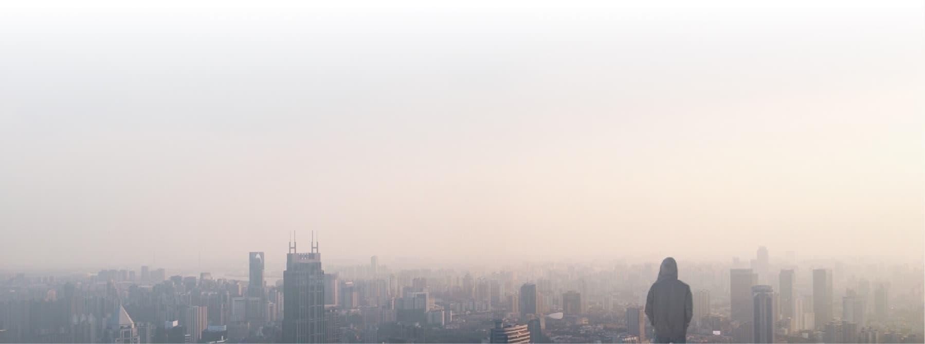 Man in hooded sweatshirt overlooking smoggy cityscape