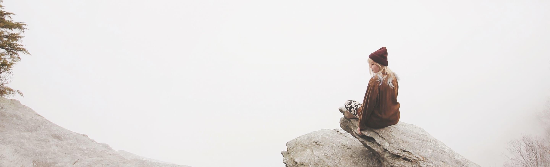 Woman sitting on edge of rock overlooking foggy landscape